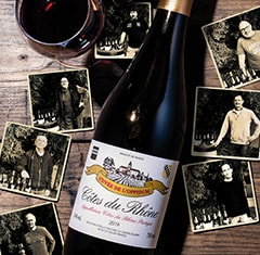 A bottle of l'Oppidum Cote-du-Rhone surrounded by old photos and a glass of wine